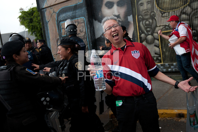 USA fans joke around with Mexican police officers in riot gear that  formed a perimeter around a bus of USA fans arriving for the USA vs. Mexico World Cup Qualifier at Azteca stadium in Mexico City, Mexico on March 26, 2013.