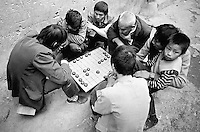 """Am Yangtze-Fluss in der Provinz Hubei / China<br /> Die chinesische Regierung plant in der Provinz Hubei den Yangtze-Fluss mit einem Staudamm zur Stromgewinnung aufzustauen. Dabei werden ca. 3 Millionen Menschen umgesiedelt.<br /> Hier: Maenner und Jungen beim traditionellen Brettspiel """"GO"""" in Zigui. Der Ort Zigui wird vom Staudamm ueberspuelt werden und mehrere tausend Menschen verlieren ihre Heimat.<br /> 1992, Zigui, Provinz Hubei / China<br /> Copyright: Christian-Ditsch.de<br /> [Inhaltsveraendernde Manipulation des Fotos nur nach ausdruecklicher Genehmigung des Fotografen. Vereinbarungen ueber Abtretung von Persoenlichkeitsrechten/Model Release der abgebildeten Person/Personen liegen nicht vor. NO MODEL RELEASE! Nur fuer Redaktionelle Zwecke. Don't publish without copyright Christian-Ditsch.de, Veroeffentlichung nur mit Fotografennennung, sowie gegen Honorar, MwSt. und Beleg. Konto: I N G - D i B a, IBAN DE58500105175400192269, BIC INGDDEFFXXX, Kontakt: post@christian-ditsch.de<br /> Urhebervermerk wird gemaess Paragraph 13 UHG verlangt.]"""
