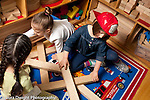 Preschool 4 year olds group of three girls playing together in block area working together, one girl wearing dressup fire hat