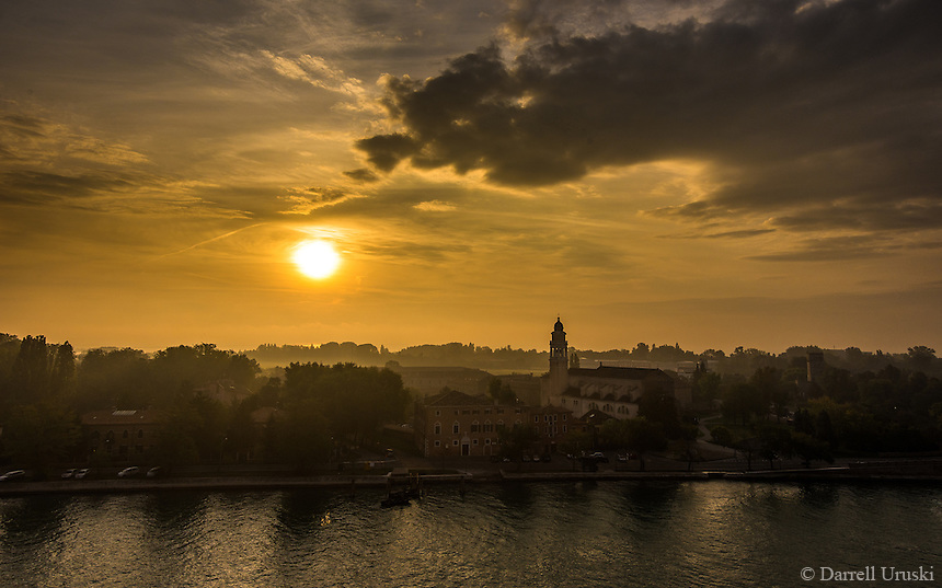 Fine Art Landscape Photograph of a golden sunrise over the city of Venice Italy. The dramatic cloud formations and church steeple blended well with this countryside viewpoint of the romantic city of Venice.