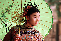 A portrait of a young Chinese woman in traditional attire holding a parasol. Xian, China..