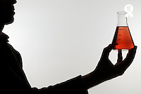 Silhouette of man holding measuring beaker (Licence this image exclusively with Getty: http://www.gettyimages.com/detail/sb10068346ce-001 )