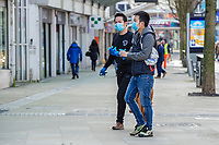 Pictured: Two masked shopper walks through Swansea City Centre during the Covid-19 Coronavirus pandemic in Wales, UK, Swansea, Wales, UK. Monday 23 March 2020