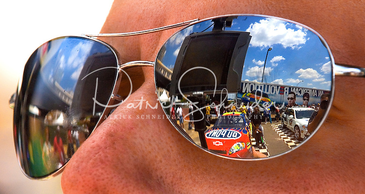 A NASCAR show car reflects in the glasses of a Speed Street participant...For several days leading up to the May races at the Lowe's Motor Speedway, uptown Charlotte streets are transformed into a showcase of motor sports and non-stop entertainment. ..Photo taken in 2007. Photographer also has images from 2008.