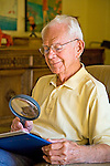 Senior man wears glasses looks through magnifying glass to view photographs in photo album and smiles remembering good times.