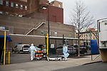 Healthcare workers wheels hospital beds inside after transporting the bodies of COVID-19 victims to a refrigerated trailer used as a temporary morgue outside of Wyckoff Heights Medical Center in the Brooklyn borough of New York City on April 5, 2020.  Photograph by Michael Nagle