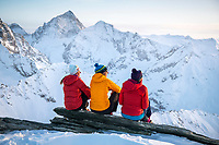 Friends relaxing and watching the sunset outside the Tracuit Hut, during a ski tour in the Swiss Alps, Zinal, Switzerland.