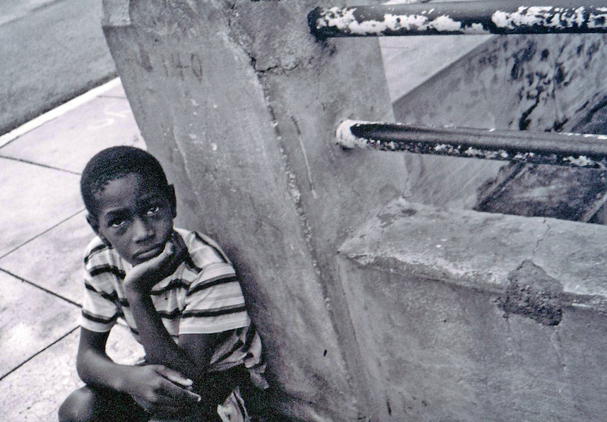 A boy sits on the curb of a side street during annual May Day celebrations in Varadero, Cuba, May 1, 2003. MARK TAYLOR GALLERY