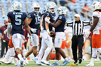 CHAPEL HILL, NC - OCTOBER 10: Sam Howell #7 of North Carolina is checked on by teammates Michael Carter #8 and Beau Corrales #15 after an 11-yard run after which he suffered a personal foul during a game between Virginia Tech and North Carolina at Kenan Memorial Stadium on October 10, 2020 in Chapel Hill, North Carolina.