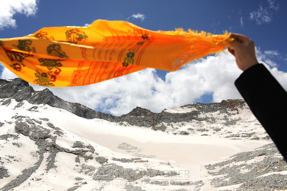 A Tibetan flag flies over the Dagu Glacier. The glacier has been shrinking in recent years, as a result of rising temperatures in the region. South-east Tibetan Plateau, in Sichuan Province, western China.