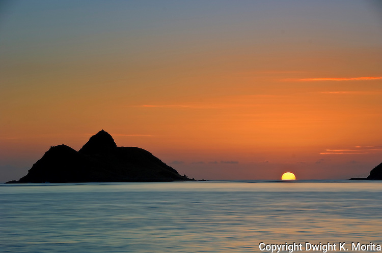 Fireball emerges from horizon between Mokulua Islands at Lanikai Beach