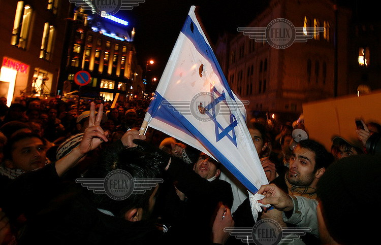 An Israeli flag is set alight in front of the parliament. Pro-Palestinian protesters clashed with police as they held a counter demonstration against pro-Israel campaigners in the Norwegian capital Oslo. Violent clashes lasted for hours  in the centre of Oslo. Both groups came to the streets as a result of the violence in Gaza. Israeli forces began a series of air strikes on the Gaza Strip on the 27th of December in retaliation against Hamas rockets fired into Israel. After eight days of bombardment, leaving over 400 Palestinians and four Israelis dead, Israeli tanks launched a ground invasion on the 4th of January.
