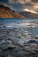 Dramatic sunset over Lake Wakatipu with surrounding mountains, Central Otago, New Zealand