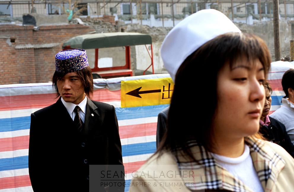 CHINA. Beijing. Two worshipers at the Niu Jie Mosque during the festival of Eid-al-Fitr, marking the end of Ramadan. 2005