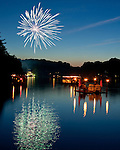 Spectators float on the lake to enjoy patriotic music and Independence Day fireworks on 4th of July at Lake Thoreau in Reston, Virginia, USA.