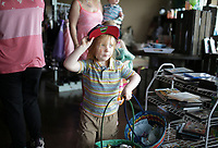 Thomas Warren, 2, of Bella Vista carries Easter baskets, Saturday, April 3, 2021 at the Oasis of Hope thrift shop Rogers. The Easter Bunny greeted guests for their prom dress and tuxedo sale. Staff gave away free Easter baskets, candy and books. Check out nwaonline.com/210404Daily/ for today's photo gallery. <br /> (NWA Democrat-Gazette/Charlie Kaijo)