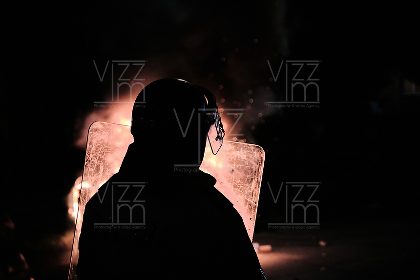 BOGOTA - COLOMBIA, 10-09-2020: Un Policía monta guardia durante el segundo día de protestas causadas por el asesinato del abogado Javier Ordoñez, abogado de 46 años, a manos de efectivos de la Policía de Bogotá el pasado miércoles 09 de septiembre de 2020 en el barrio Villa Luz al noroccidente de Bogotá (Colombia). En lo que va corrido del 2020 la alcaldía de Bogotá ha recibido 137 denuncias  de abuso policial de las cuales la Policía acusa recibido de 38.  / A policeman stands guard during the second day of protests caused by the murder of lawyer Javier Ordoñez, a 46-year-old lawyer, at the hands of members of the Bogotá Police on Wednesday, September 9, 2020 in Villa Luz neighborhood in the northwest of Bogotá (Colombia). So far in 2020 the Bogotá mayor's office has received 137 complaints of police abuse of which the Police accuse they have received 38. Photo: VizzorImage / Alejandro Avendaño / Cont