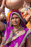 Abnaheri, Rajasthan, India.  Woman Carrying Pots on her Head as she Participates in a Pre-wedding Celebration.