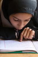 Surman, Libya.  Girl Studying Koranic Verses in the Madrasa of Sidi Rashid al-Galili.  Young girls wear the traditional Libyan head scarf.
