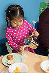 Education Preschool 3-4 year olds meal time girl pouring milk into glass holding container with her left hand