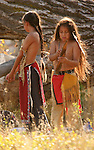 Two young Native American Indian boys playing with sticks by a large fallen willow tree