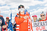 """A woman wears Trump 2020 campaign shirt, hat, and earrings, and a facemask reading """"Tastes like socialism"""" and holds a Trump campaign flag and American flag while holding her hand up to her heart during the Pledge of Allegiance as people gather for an anti-lockdown protest organized by the alt-right group Super Happy Fun America near the home of Massachusetts governor Charlie Baker in Swampscott, Massachusetts, on Sat., May 16, 2020. The woman carried a sign reading """"WWG1WGA / Q / #Obamagate"""" which are references to the QAnon conspiracy theories prevalent among fringe conservative circles. """"Obamagate"""" has recently been talked about by US President Donald Trump without reference to what the """"Obamagate"""" scandal might be. The protest was in defiance of Massachusetts orders mandating face coverings and social distancing and prohibiting gatherings larger than 10 people during the ongoing Coronavirus (COVID-19) global pandemic. The state's stay-at-home order is expected to be updated on May 18, 2020, with a phased reopening plan issued by the governor as COVID-19 cases continue to decrease. Anti-lockdown protests such as this have become a conservative cause and have been celebrated by US president Donald Trump. Many of the protestors displayed pro-Trump messages or wore Trump campaign hats and shirts with phrases including """"Trump 2020"""" and """"Keep America Great."""" Super Happy Fun America, organizers of the protest, are an alt-right organization best known for creating the 2019 Boston Straight Pride Parade."""