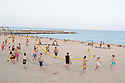 Spain - Barcelona - Youngsters moving a beach volley net on the beach.