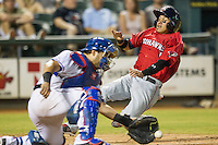 Oklahoma City RedHawks third baseman Ronny Torreyes (5) slides home during the Pacific Coast League baseball game against the Round Rock Express on August 1, 2014 at the Dell Diamond in Round Rock, Texas. The Express defeated the RedHawks 6-5. (Andrew Woolley/Four Seam Images)