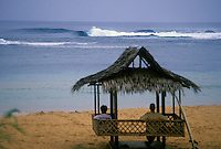 Surfer sitting in thatched hut with surfboard watching perfect waves, Philippines