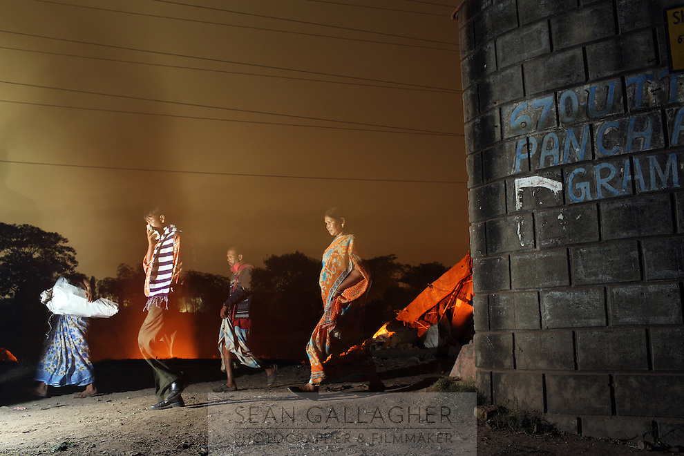Kolkatans walk past a fire burning plastics in the Topsia Street district, in the east of the city. The area is notable for its informal plastic recycling industry. Waste is often discarded and burnt in the evenings. India. November, 2013