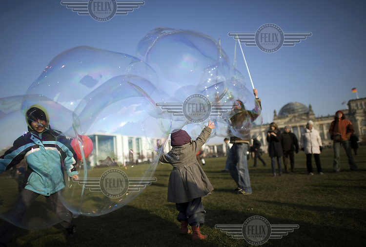 Children play with giant bubbles during a protest, outside the Reichstag. The march is linked to the Occupy Movement, a worldwide protest against the banking industry and the prevailing economic system.