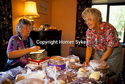 'ENGLISH VILLAGE FETE', TWO LADIES FROM THE VILLAGE FETE ORGANISING COMMITTEE, PRICING CAKES AND JARS OF JAM MADE BY VILLAGERS FOR THE AUGUST SUMMER FETE. 1993 1990s UK