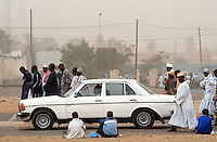 Senegal. Dakar. On each friday, muslim people go to the mosk, kneel down and pray for Allah. Once the religious service finished, they go back home. A white Mercedes is on its way.Desert's wind , harmattan, blows sand dust over the city. © 2000 Didier Ruef