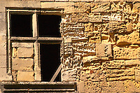 A black empty window in a falling down house with an old stone wall in the medieval village of Saint Emilion, Bordeaux