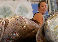 Fish vendor and the eyes of the fish, Phnom Penh market, Cambodia