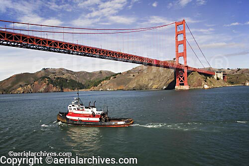 aerial photograph tug boat approaching Golden Gate bridge San Francisco Marin headlands in background