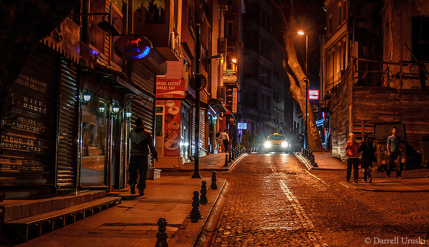 Fine Art Landscape Photograph. Nighttime in Istanbul, Turkey. <br /> This low key street scene has several elements that portray night life in Istanbul.<br /> The Taxi draws you eyes into the scene with it's bright headlights. The people who are walking add motion, and the people standing bring a relaxed atmosphere to this warm evening night in Istanbul.