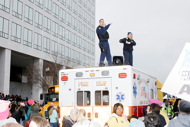 Police stand on an ambulance directing traffic as people gather in the National Mall area of Washington, DC, for the Women's March on Washington protest and demonstration in opposition to newly inaugurated President Donald Trump on Jan. 21, 2017.