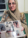 Iran 2004  Une Kurde de Sardasht , victime des armes chimiques utilisées par les Irakiens  pendant la guerre Iran-Irak, montrant des photos de membres de sa famille morts suite aux bombardements.<br /> Iran 2004  A Kurdish woman from Sardasht, victim of chemical weapons , after the bombing of her city by the Iraqis, shows photos of her dead relatives because of the bombing<br /> ئیران 2004 , ئه و کورده خه لکی سه رده شته , له گه ل بنه ماله که ی تووشی بومبارانی کیمیاوی بووه که عییراقییه کان له کاتی شه ری  ئیران  و  عیراق به کارییان هیناوه. لیره , وینه ی ئه ندامانی بنه ماله که ی که له بومبارانی کیمیاوی کوژراون , نیشان ده دات