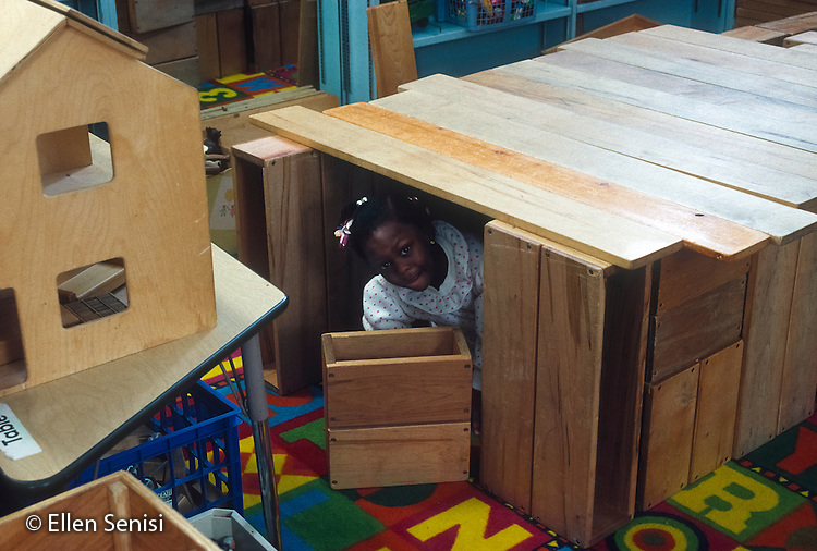 MR / Schenectady, NY. Yates Arts in Education Magnet Elementary School. Pre-K. Girl (4, African-American) peeks out of pretend house constructed with large blocks during free playtime. MR: Jon2. © Ellen B. Senisi