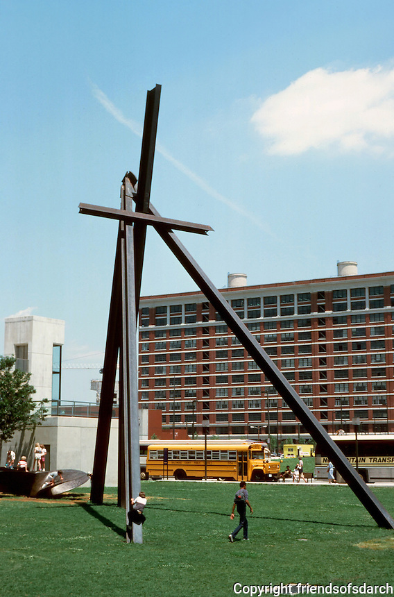 "Baltimore: # 10.   Inner Harbor-Cor-Ten Steel Beam Sculpture ""Under Sky/One Family""  by Mark Di Suvero, 1980.  Four beams placed vertically with fifth beam resting horizontally. To the left, another sculpture--a propeller blade resting in a bed of bark chips.   Photo '85."