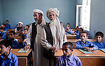 9 June 2013, Baba Kohna village, Deh Dadi District, Mazar-i-Sharif, Balkh Province, Afghanistan.   Mr. Mohammad Hanif (right), leader of the village shura and Hajji Zaher (left) in class with students at Ghulam Hazrat Khan Primary School in Baba Kohna Village, Deh Dadi District. A new school building is being constructed on the site to accomodate high school students as well as primary. The schools' buildings have been built under the National Solidarity Program which gives local shura councils the opportunity to decide what facilities they need most in the community. Instead of opting for things like electricity, a road bridge, or water services the community was adamant a school was the priority. Previously if kids wanted to go to school the nearest was over 10kms away.  The NSP is the Governments national flagship program to support small scale reconstruction and development activities identified by CDC's across the country.About 80% of community sub projects involve infrastructure such as irrigation, roads and electricity all critical for the recovery of the rural economy and governance.The ministry of Rural Rehabilitation and Development is implementing the program. Picture by Graham Crouch/World Bank