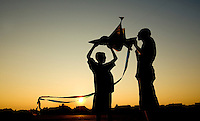 Two boys are silhouetted as they work to fly a kite on the beaches of Sullivan's Island, near Charleston, SC. Model release.