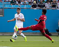 CHARLOTTE, NC - JUNE 23: Marcus Godinho #23 passes towards the goal past Daniel Morejon #5 during a game between Cuba and Canada at Bank of America Stadium on June 23, 2019 in Charlotte, North Carolina.