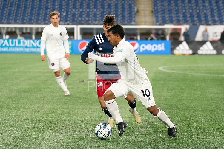 FOXBOROUGH, MA - OCTOBER 09: Eduardo Sosa #10 of Fort Lauderdale CF drives forward as Nicolas Firmino #29 of New England Revolution II comes in to tackle during a game between Fort Lauderdale CF and New England Revolution II at Gillette Stadium on October 09, 2020 in Foxborough, Massachusetts.