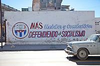 """Cuba, Havana.  Political Slogan: More United and Combative, Defending Socialism.""""  1954 Buick."""
