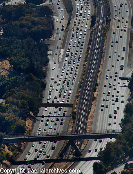 aerial photograph of Friday afternoon rush hour traffic on Highway 24 at Lafayette, Contra Costa County, California.  The Bay ARea Rapid Transit (BART) tracks run between the two directions of freeway and enter the underpass to the intersection of Highway 24 and Interstate 680 at Walnut Creek in the foreground