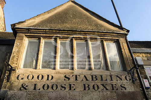 """Stamford, Lincolnshire, England Old Millstone pub """"Good Stabling and loose boxes"""" on the wall."""