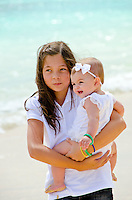 Leilani holding baby sister Emma at the beach