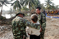 Thai soldiers comfort a woman who lost family members in the tsunami which struck South Asia on 26/12/2004. Up to 3,000 people, half the population, were feared dead in the fishing village of Baan Nam Kem.An underwater earthquake measuring 9 on the Richter scale triggered a series of tidal waves which caused devastation when they struck dry land. 12 countries were affected by the tsunami, with a combined death toll of over 150,000. © Fredrik Naumann